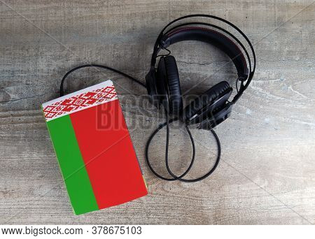Headphones And Book. The Book Has A Cover In The Form Of Belarus Flag. Concept Audiobooks. Learning