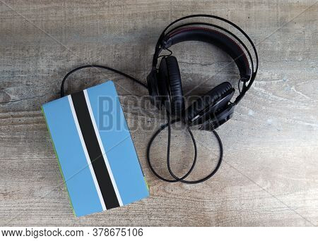 Headphones And Book. The Book Has A Cover In The Form Of Botswana Flag. Concept Audiobooks. Learning