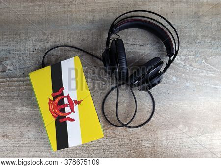 Headphones And Book. The Book Has A Cover In The Form Of Brunei Flag. Concept Audiobooks. Learning L