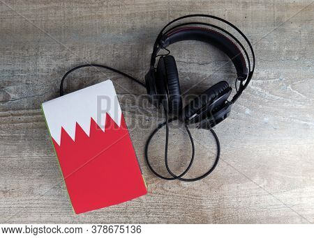 Headphones And Book. The Book Has A Cover In The Form Of Bahrain Flag. Concept Audiobooks. Learning