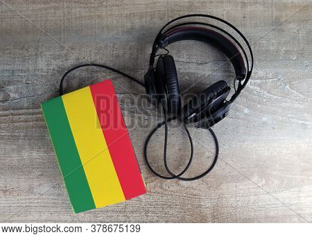 Headphones And Book. The Book Has A Cover In The Form Of Bolivia Flag. Concept Audiobooks. Learning