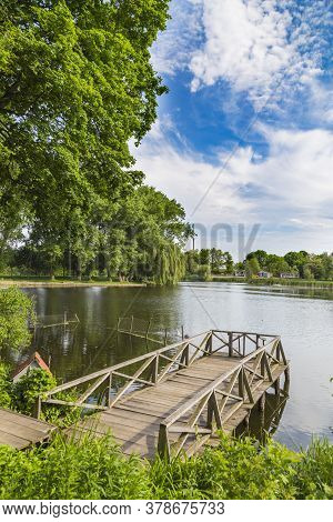 Summer View  On The Lake With A Wooden Bridge. Landscape Park In The Palace And Park Ensemble In Vil