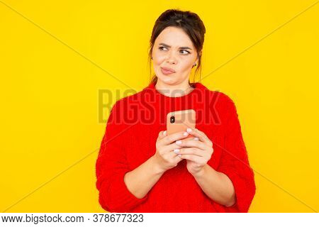 Thinking Young Woman With Phone Isolated Over The Yellow Backgroung.