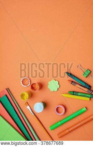 School Supplies On Orange Color Background, Top View, Copy Space