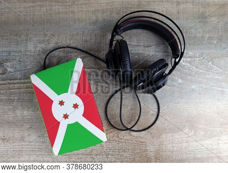 Headphones And Book. The Book Has A Cover In The Form Of Burundi Flag. Concept Audiobooks. Learning