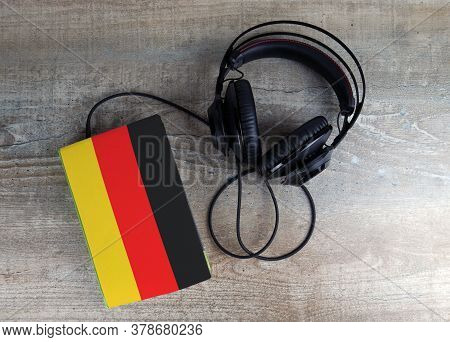 Headphones And Book. The Book Has A Cover In The Form Of Germany Flag. Concept Audiobooks. Learning
