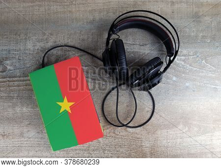 Headphones And Book. The Book Has A Cover In The Form Of Burkina Faso Flag. Concept Audiobooks. Lear