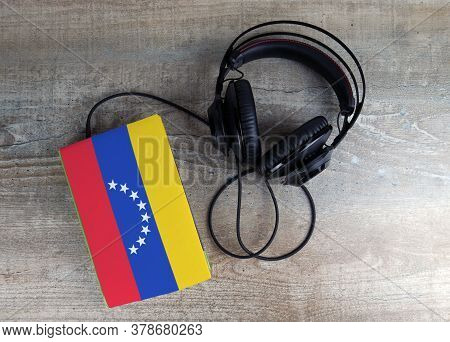 Headphones And Book. The Book Has A Cover In The Form Of Venezuela Flag. Concept Audiobooks. Learnin