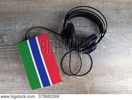 Headphones And Book. The Book Has A Cover In The Form Of Gambia Flag. Concept Audiobooks. Learning L