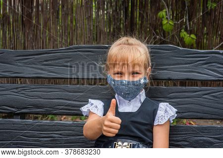 Schoolgirl Girl In A Protective Mask. Back To School Soon. Pandemic, Prevention, Protection, Schoolg