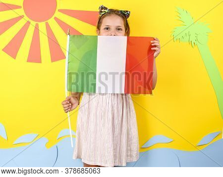 Little Girl On A Bright Background With Italian Flag. The Concept Of Summer, Beach Holidays And Vaca