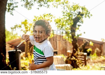 Happy African Boy Playing With Soap Bubbles In Nature