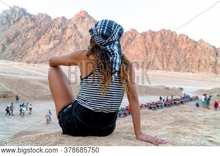 A Beautiful Girl In Black Shorts And Kefiah Admires Particular Egyptian Red Hills.