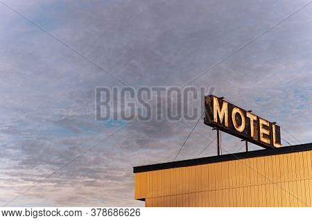 Motel Neon Sign Over A Sunset Cloudy Sky