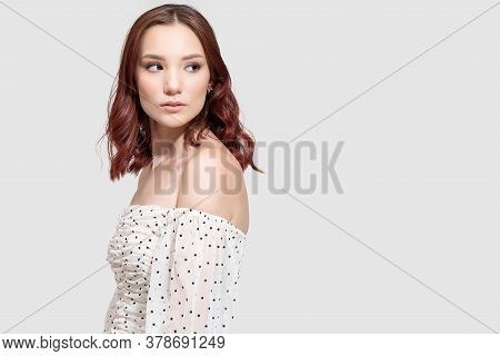 Side View Of Elegant Female Fashion Model Standing With Sideways Glance