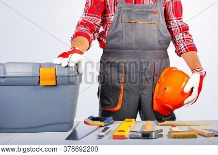 Workman In Grey Overall With Tool Box And Tools On The Table. House Repair Concept.