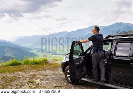 Happy Traveler Man Standing On His Car On Mountains Top. Caucasian Male On Road Trip Enjoying Mounta