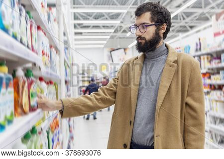 Young Man In The Supermarket In The Household Chemicals Department. Large Selection Of Products. A B