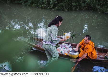23 Jul 2020 - Woman Giving Food To Buddha In The Boat At House Of Passion Hotel In Amphawa Thailand.