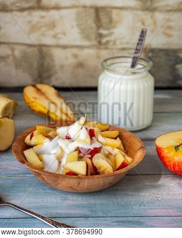 Fruit Salad In Deep Bamboo Plate With Natural Yoghurt And Glass Jar With Yoghurt