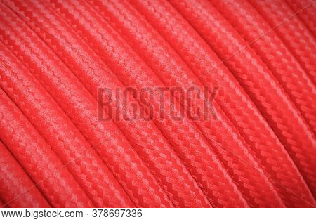 Red Electric Cable As Background Texture. Place For Text Or Inscription