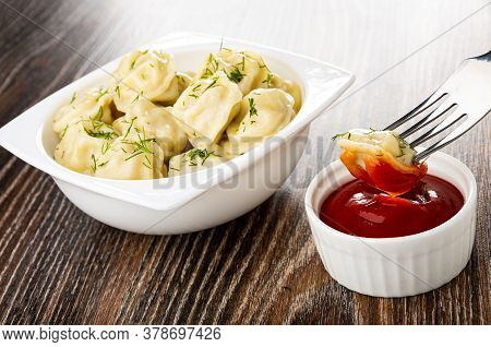White Glass Bowl With Meat Dumplings And Dill, Dumpling Strung On Fork Above Bowl With Ketchup On Da