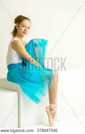 Adorable Little Girl Putting On Her Ballet Dancing Shoes, Sitting On The Floor At A Dance Studio. Li