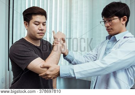 Asian Physiotherapists Check The Elbows Of Patients Who Have Undergone Orthopedic Rehabilitation.