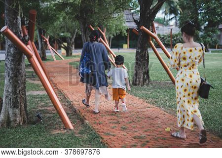 Grandmother Holding Hand Of Grandchildren Walking In The Park.