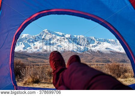 Tent Lookout On A Camp In The Mountains. Feet Hiker Relaxing Enjoying View From Tent Camping Entranc