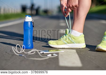 Runner Woman Tying Running Shoes Laces Getting Ready For Race On Run Track Stadium With Bottle Of Wa