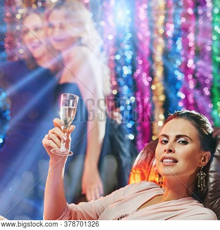 Portrait Of Attractive Happy Woman Drinking Champagne In Night Club
