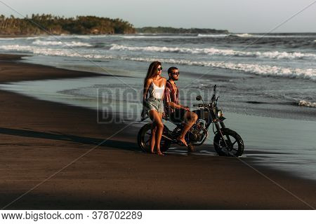 Stylish Couple On A Motorbike By The Sea. Couple In Love At Sunset By The Sea. Beautiful Couple On A