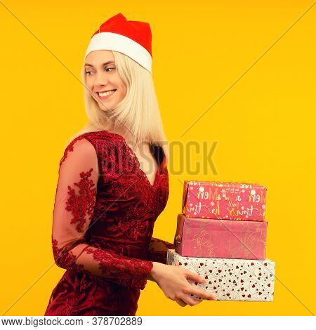 A Beautiful Sexy Girl In A New Year's Hat And Gray Dress, Hold In Hands Gifts On Yellow Background.