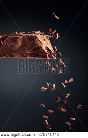 Large Piece Of Dark Chocolate And Falling Chocolate Crumbs On A Black Background.