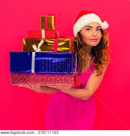 A Beautiful Sexy Girl In A New Year's Hat, Hold In Hands Gifts On Red Background. Celebration Of Chr