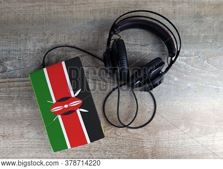 Headphones And Book. The Book Has A Cover In The Form Of Kenya Flag. Concept Audiobooks. Learning La