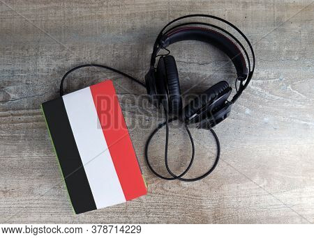 Headphones And Book. The Book Has A Cover In The Form Of Yemen Flag. Concept Audiobooks. Learning La