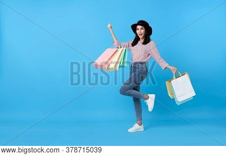 Happy Young Thai Asian Female Carrying With Both Arms Raised In A Ecstatic Gesture And Shopping Bags