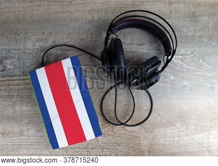 Headphones And Book. The Book Has A Cover In The Form Of Costa Rica Flag. Concept Audiobooks. Learni