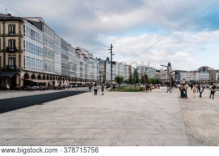 Corunna, Spain - July 20, 2020: View Of Marina Avenue With Unknown People Walking And Houses With Fa