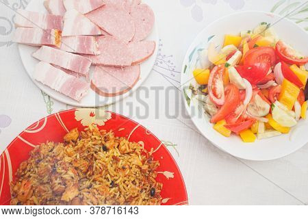 Eastern Cuisine. Red Plate With Pilaf On The Table. A Plate With Salad. Sliced Plate Of Brisket And