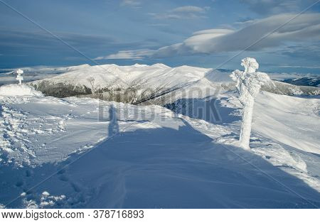 Winter Mountain Landscape With A Shadow Of The Photographer And A Cross Covered With Rime