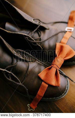 Close-up Of Orange Groom Bow Tie On Brown Mens Boots With Untied Laces On The Parquet Floor.