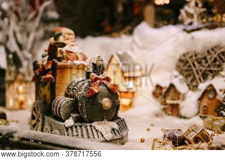 Christmas Figurine Of A Train With A Red Bow On A Showcase With Artificial Snow.