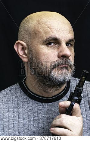 Bald Bearded Middle-aged Man With A Pistol In His Hand On The Dark Background