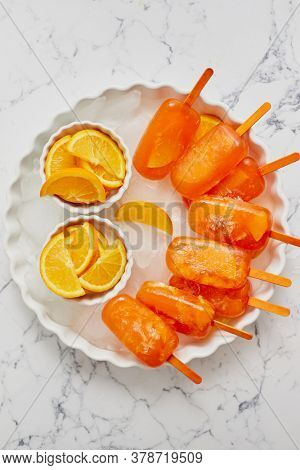 Homemade, juicy, orange popsicles. Placed on a white plate with ice cubes. Flat lay on white marble with fresh orange slices. Top view.