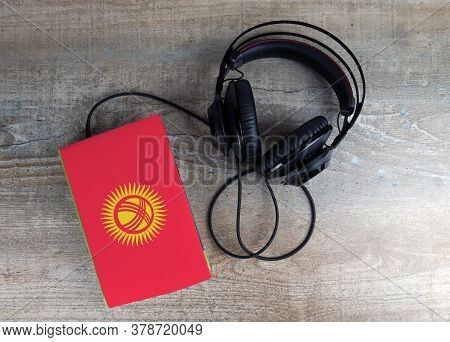 Headphones And Book. The Book Has A Cover In The Form Of Kyrgyzstan Flag. Concept Audiobooks. Learni