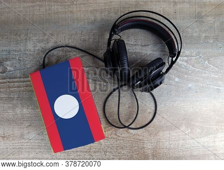 Headphones And Book. The Book Has A Cover In The Form Of Laos Flag. Concept Audiobooks. Learning Lan