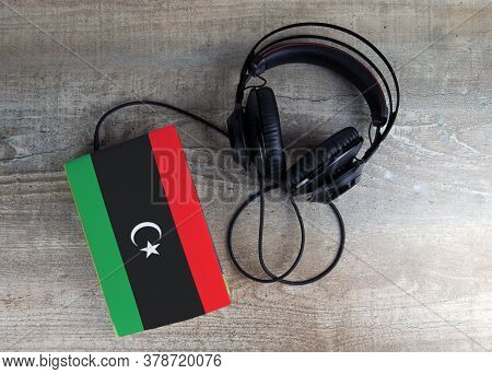 Headphones And Book. The Book Has A Cover In The Form Of Libya Flag. Concept Audiobooks. Learning La